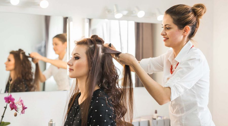 Hairdresser coiffeur makes hairstyle.