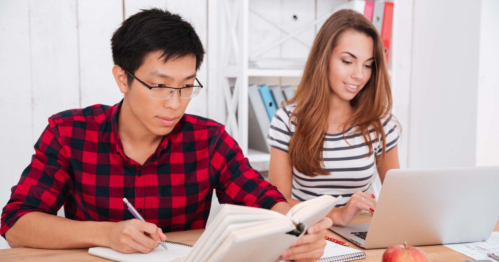 Photo of cheerful students looking at book and laptop