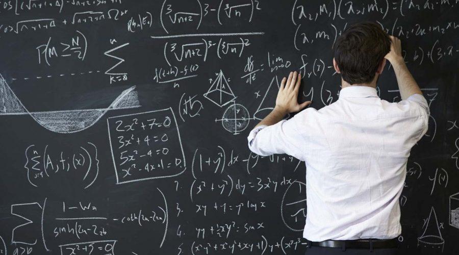 Young man writing on blackboard