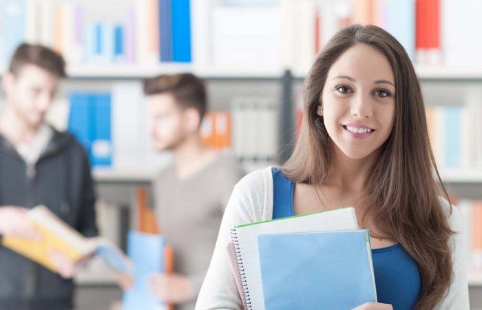 Confident smiling student holding notebooks